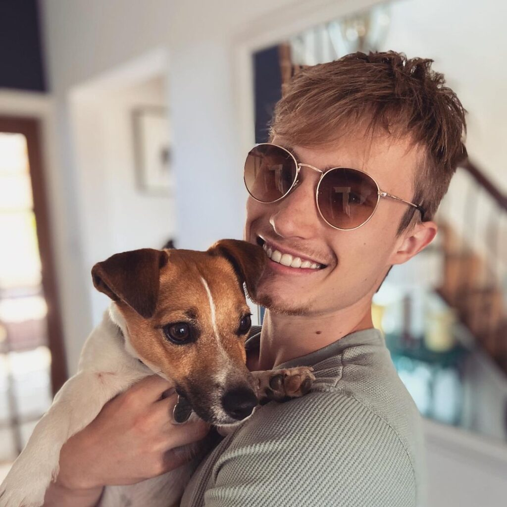 Young man in sun glasses holds dog: Jack Laugher